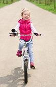 Kleines mädchen mit ihrem fahrrad — Stockfoto