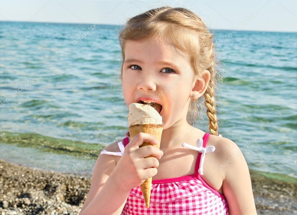 可爱的小女孩上海滩度假吃冰淇淋