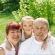 Outdoors portrait of grandparents with granddaughter  — Stock Photo