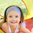Smiling little girl lying inside colorful tent — Stock Photo