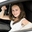 Portrait of young smiling woman holding key in his own car — Stock Photo
