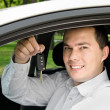 Portrait of young handsome man holding key in his own car — Stock Photo