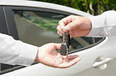 Man handing another person automobile keys new car — Stock Photo
