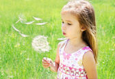 Beautiful little girl blowing dandelion — Stock Photo
