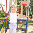 Stock Photo: Happy little girl on outdoor playground equipment