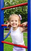 Little girl on outdoor playground equipment — Stock Photo