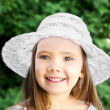 Portrait of adorable smiling little girl in white hat — Stock Photo