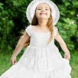Portrait of adorable smiling little girl in white dress and hat — Stock Photo