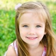 Cute smiling little girl on meadow — Stock Photo #27358077