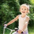 Smiling cute little girl with her bicycle — Stock fotografie