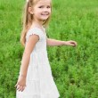 Smiling little girl is walking on the green field — Stock Photo