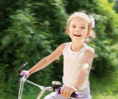 Smiling cute little girl with her bicycle — ストック写真