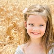 Adorable smiling little girl in the wheat field  — Stock Photo