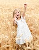 Rozkošný usměvavá holčička v poli pšenice — Stock fotografie