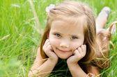Cute little girl lying in grass — Stock Photo