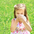 Stock Photo: Little girl is blowing her nose on green meadow