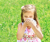 Little girl is blowing her nose on green meadow — Stock Photo