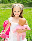 Cute little girl with her toy carriage and doll — Stock Photo