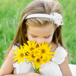 Cute little girl smelling flowers on the meadow  — Stock Photo