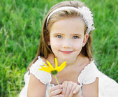 Cute little girl on the meadow with flower — Foto de Stock