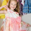Stock Photo: Cute smiling little girl chooses dress from wardrobe