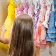 Little girl chooses dress from the wardrobe — Stock Photo