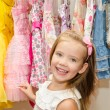 Stock Photo: Smiling little girl chooses dress from wardrobe