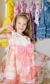 Cute smiling little girl chooses a dress from the wardrobe — Stock Photo