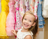 Smiling little girl chooses a dress from the wardrobe — Stock Photo