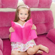 Stock Photo: Little girl reading book and siting on sofa
