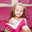 Little girl reading a book and siting on the sofa — Stock Photo