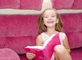 Küçük kız bir kitap okuma gülümseyerek — Stok fotoğraf