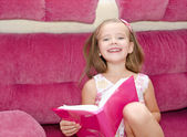 Smiling little girl reading a book — Foto de Stock