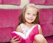 Mała dziewczynka, czytając książkę i usytuowanie na kanapie — Zdjęcie stockowe