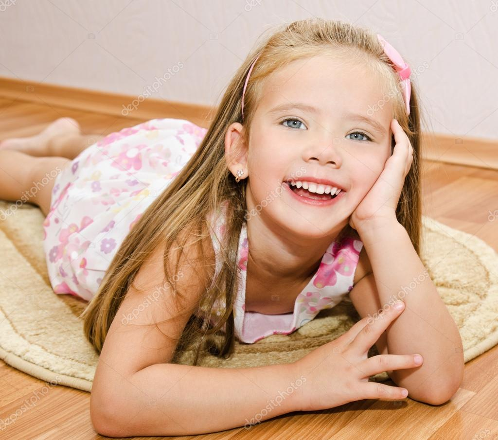 微笑着可爱的小女孩在家里地板上说谎– 图库图片
