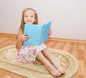 мило улыбается девочка, читая книгу — Стоковое фото
