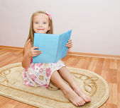 Linda sonriente niña leyendo un libro — Foto de Stock