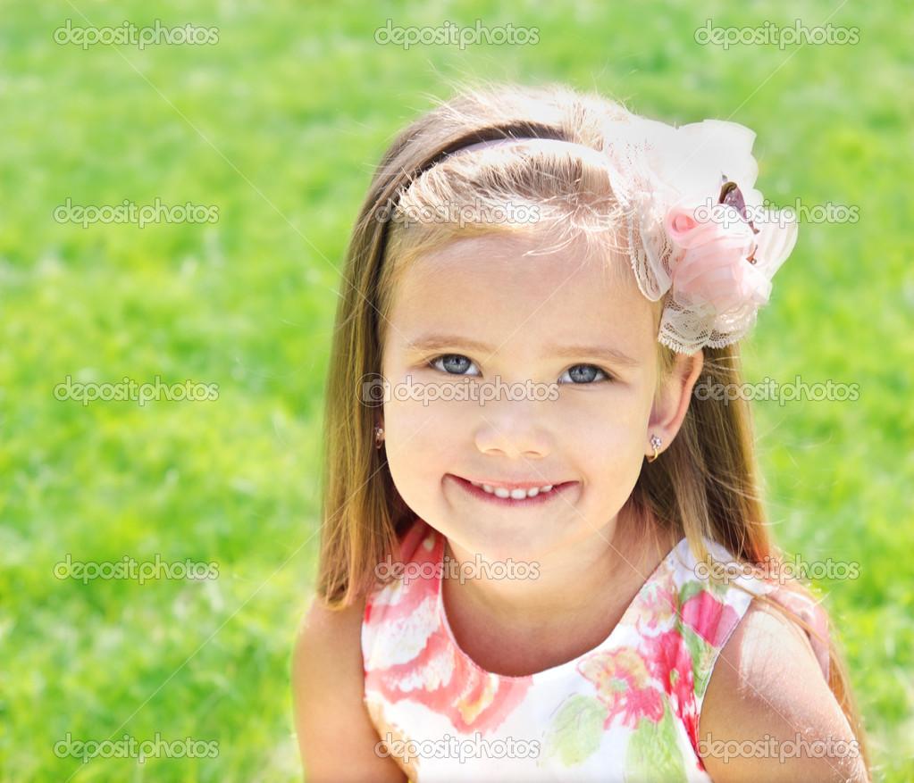 可爱微笑的小女孩在草地上