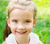 Мило улыбается девочка на лугу — Стоковое фото