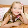 Smiling little girl lies on a house floor — Stock Photo