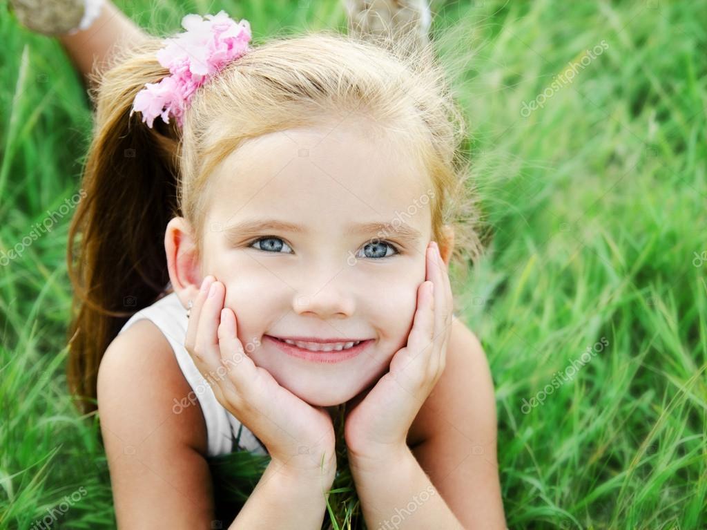 可爱微笑的小女孩躺在草地上的草在夏季的一天