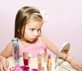Child cosmetics Cute little girl looking in the mirror — Stock Photo
