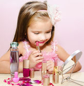 Child cosmetics Cute little girl with lipstick and mirror — Stock Photo