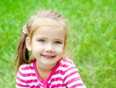 Portrait of cute smiling little girl on the meadow — Stock Photo