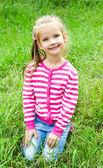 Ragazza sorridente carina sdraiato nell'erba sul prato — Foto Stock