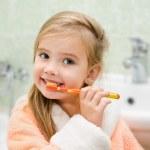 Smiling little girl brushing teeth — Stock Photo