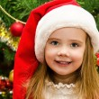 Little girl in santa hat with present have a christmas — Stock Photo #32584705