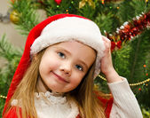 Little girl in santa hat with present have a christmas — Stock Photo