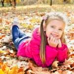 Autumn portrait of cute little girl lying in maple leaves — Stock Photo #33275709