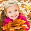 Autumn portrait of cute smiling little girl with maple leaves — Stock Photo #33275715